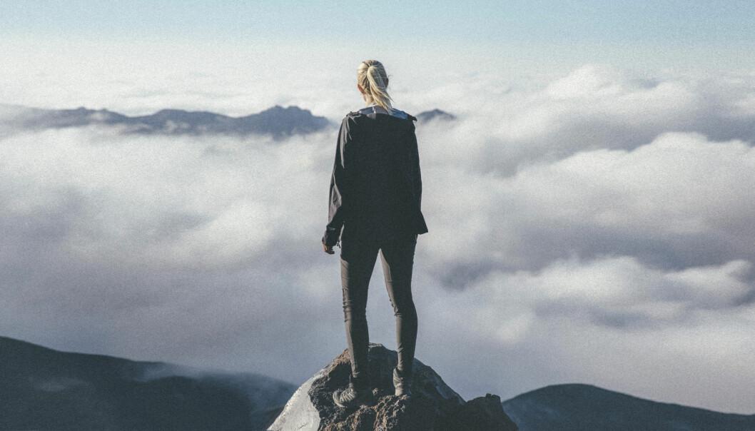 Emma står på en bergstopp och blickar ut över molnen.