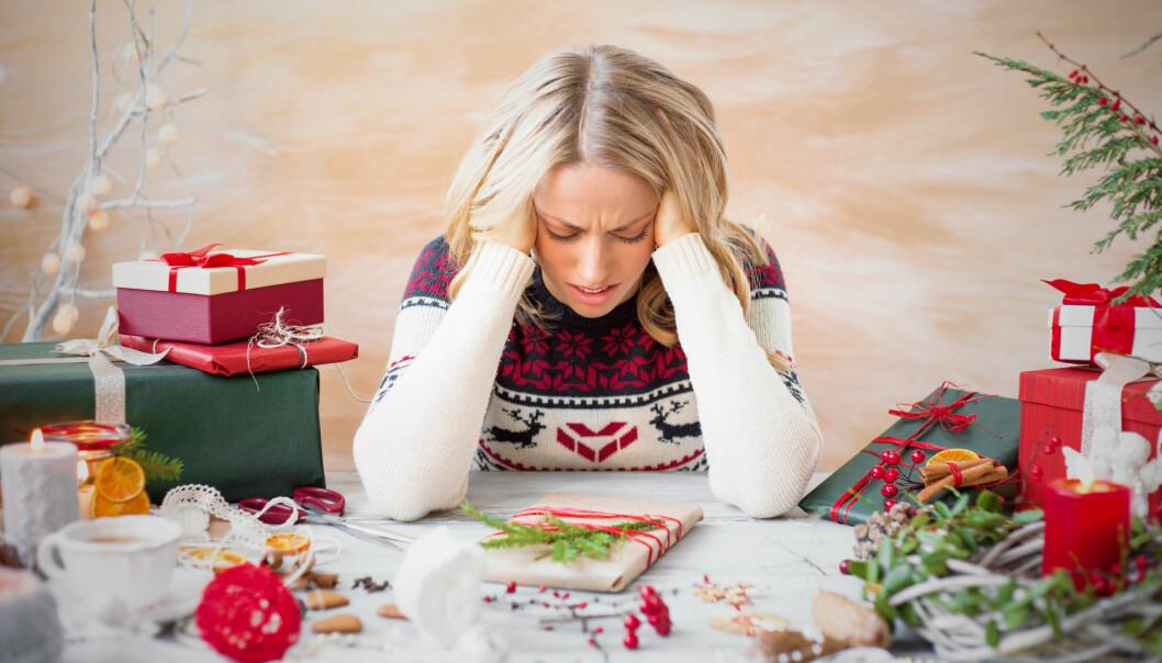 Stressad kvinna sitter vid ett bord och stirrar på julpynt och julklappar.