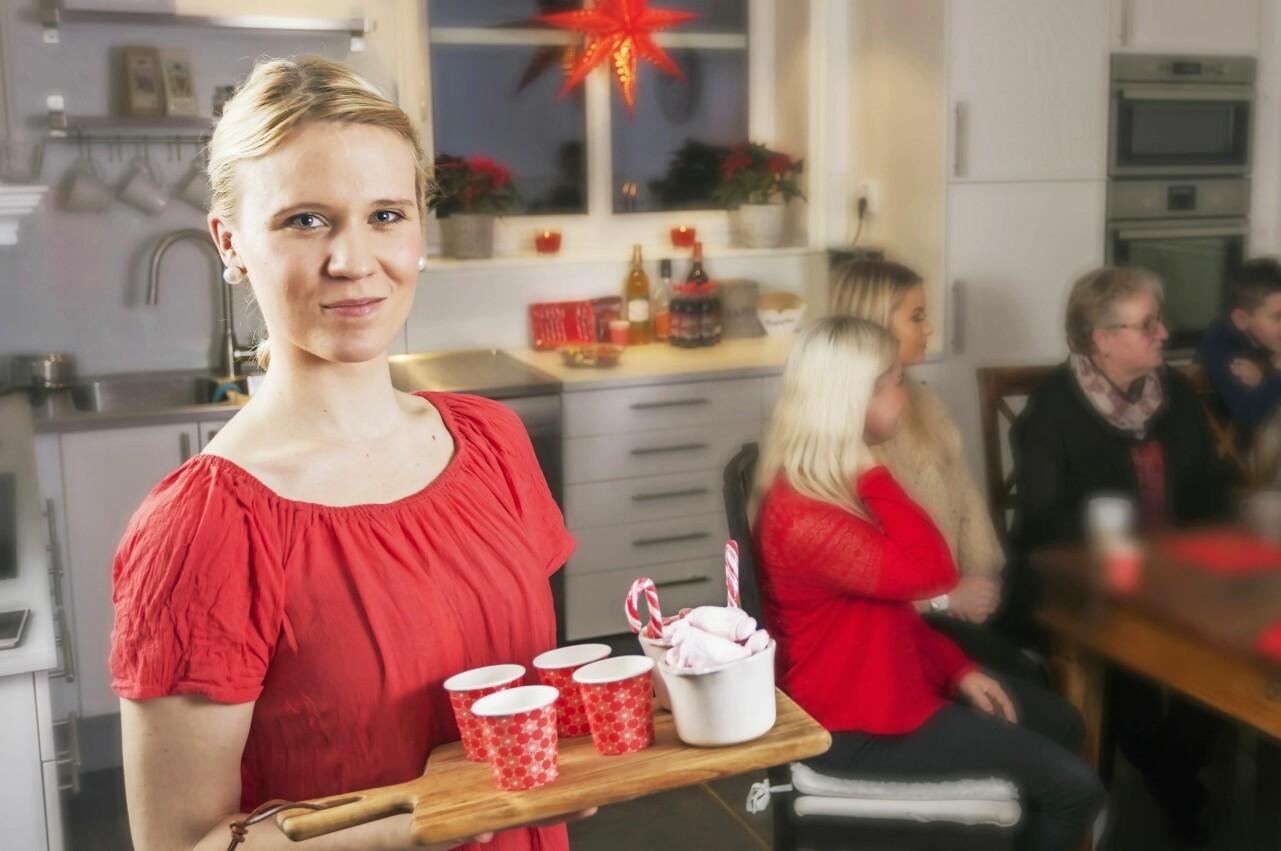 Malin i röd blus serverar glögg i sitt julpyntade hem.