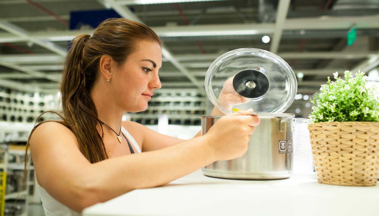 Kvinna undersöker en kastrull från Ikea.