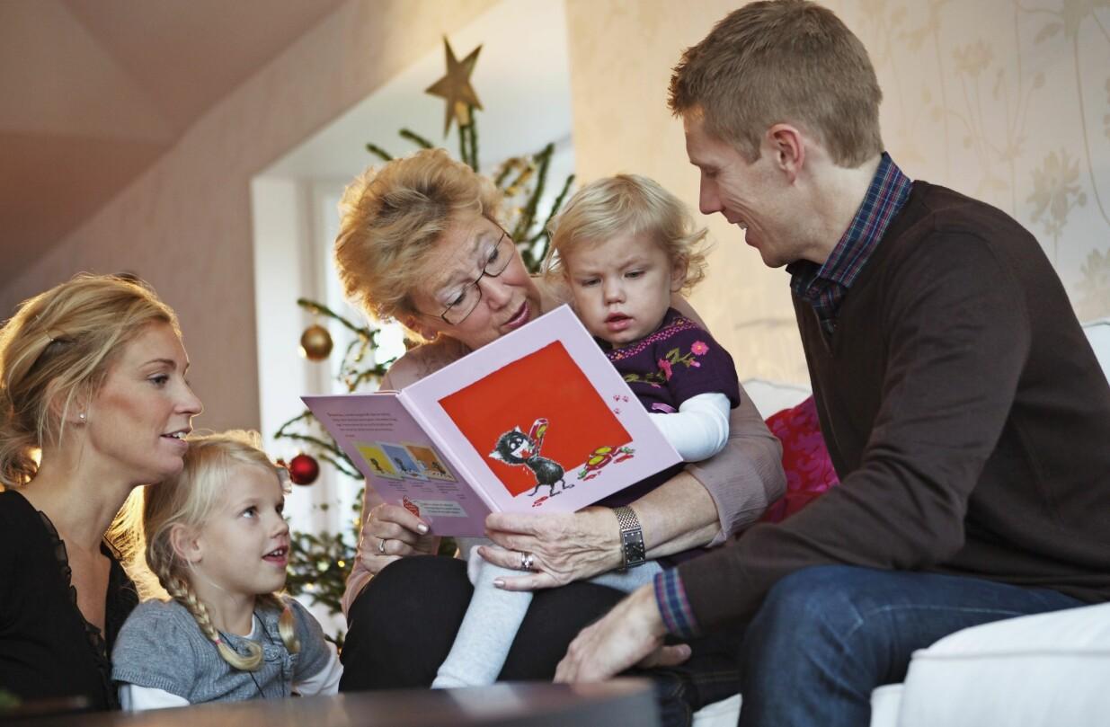 Familj sitter tillsammans framför en julgran och läser en bok.