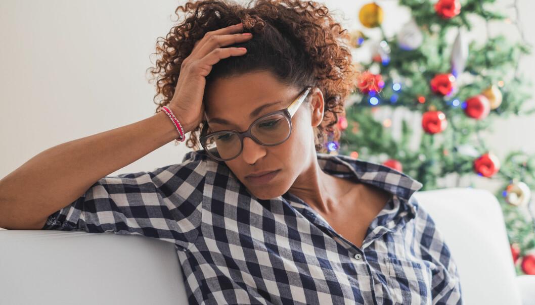 Sönderstressad kvinna sitter i en soffa i ett julpyntat vardagsrum.