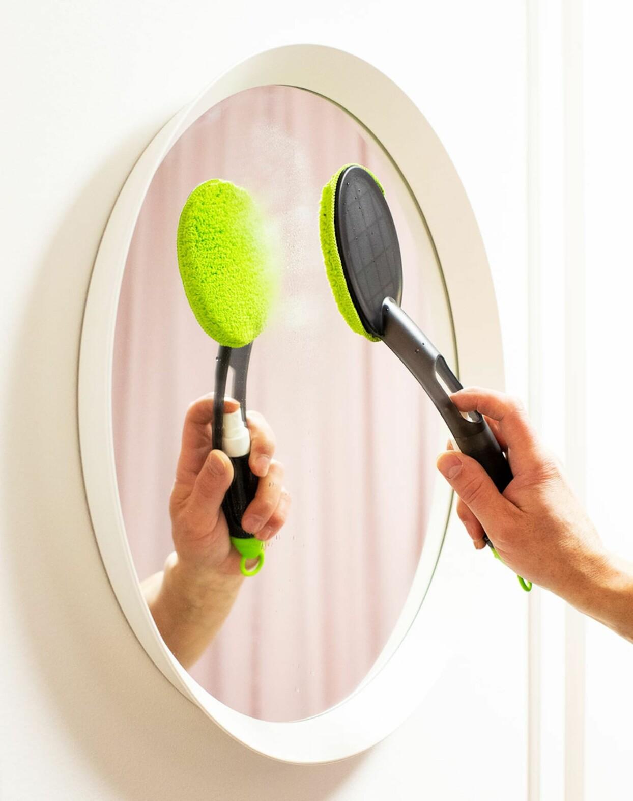 Spegel som putsas med microfiberverktyg.