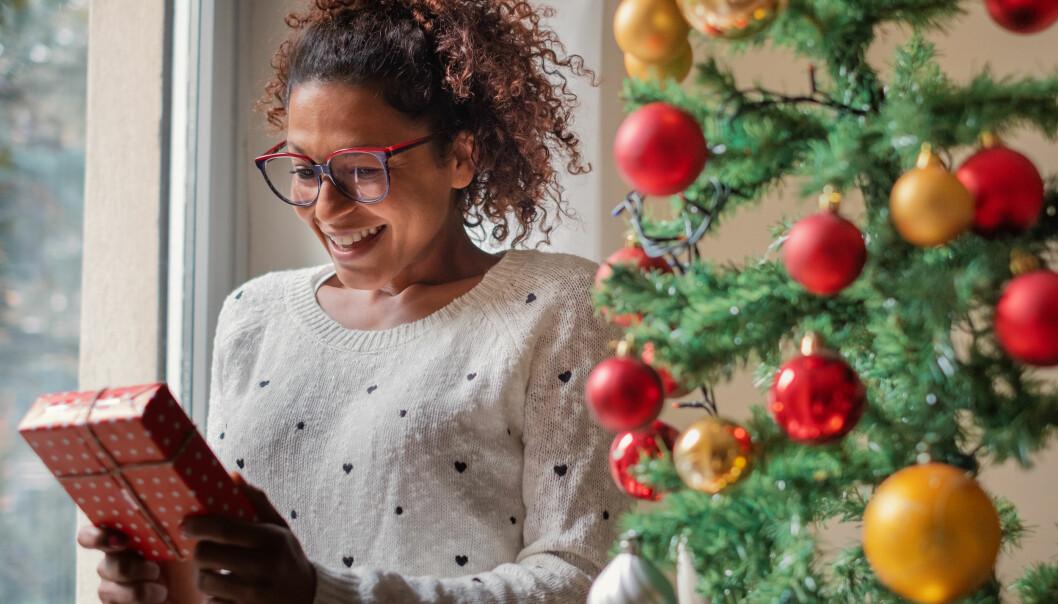 Ensam, glad kvinna håller en julklapp i handen vid en julgran.
