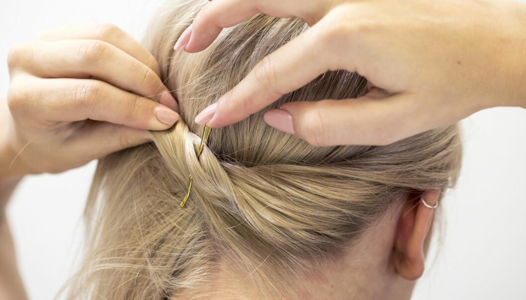 Kvinna visar hur hon tvinnar håret för att skapa en fin festfrisyr.