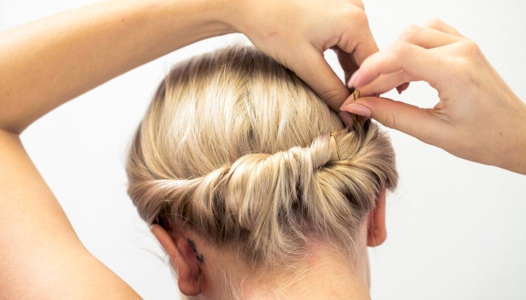 Kvinna fäster sin enkla och fina festfrisyr med en hårklämma.