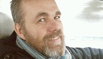 Närbild på en glad Svein Jemtland med skägg, som kör bil, privatfoto från tidigare.