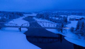 Älv med bro över i snölandskap