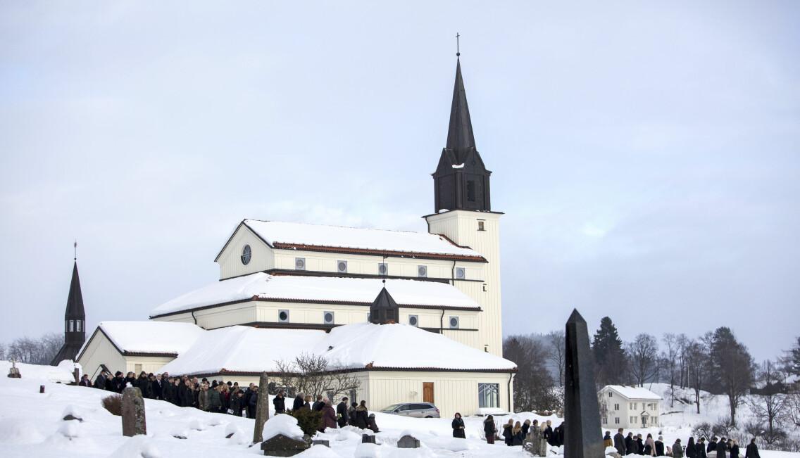 Kyrka i snölandskap med begravningsprocession