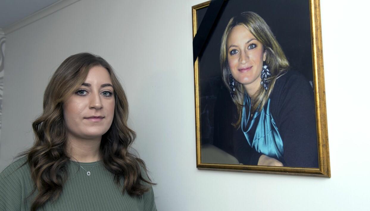 Jennifer står vid en vägg där det hänger ett inramat foto av hennes mamma Carla.