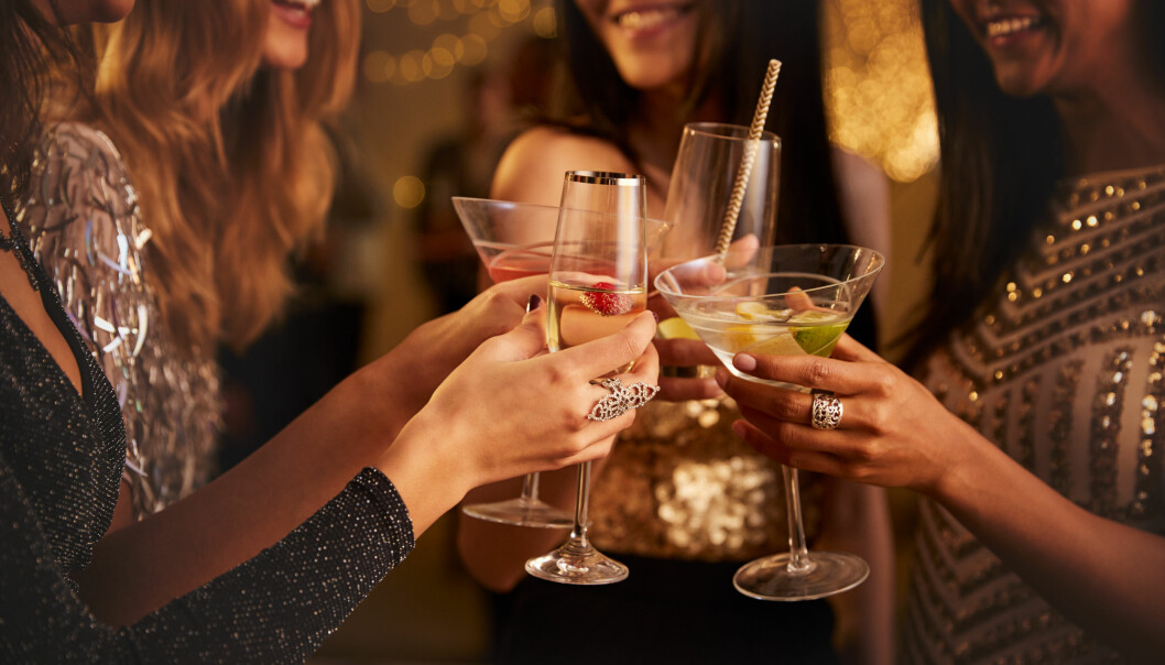 Vänner på fest skålar med sina drinkar.