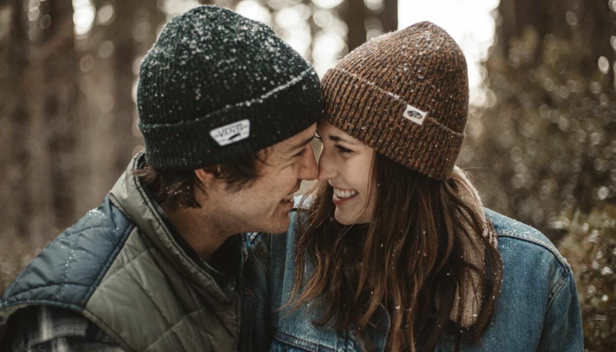 Man och kvinna sitter tätt tillsammans i ett vinterlandskap.