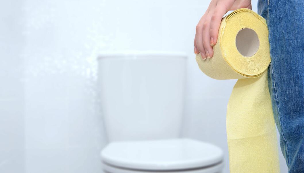 Kvinna på toalett med en rulle gult toalettpapper i handen.