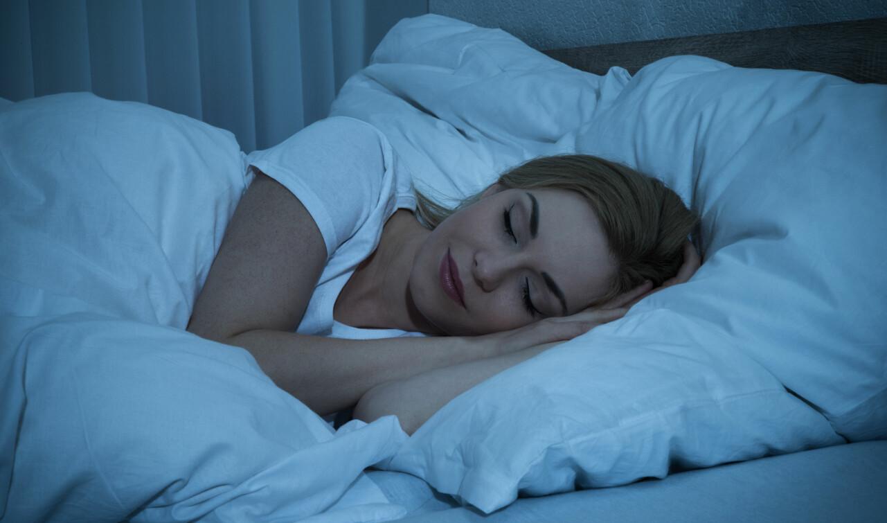 Sovande kvinna i säng.