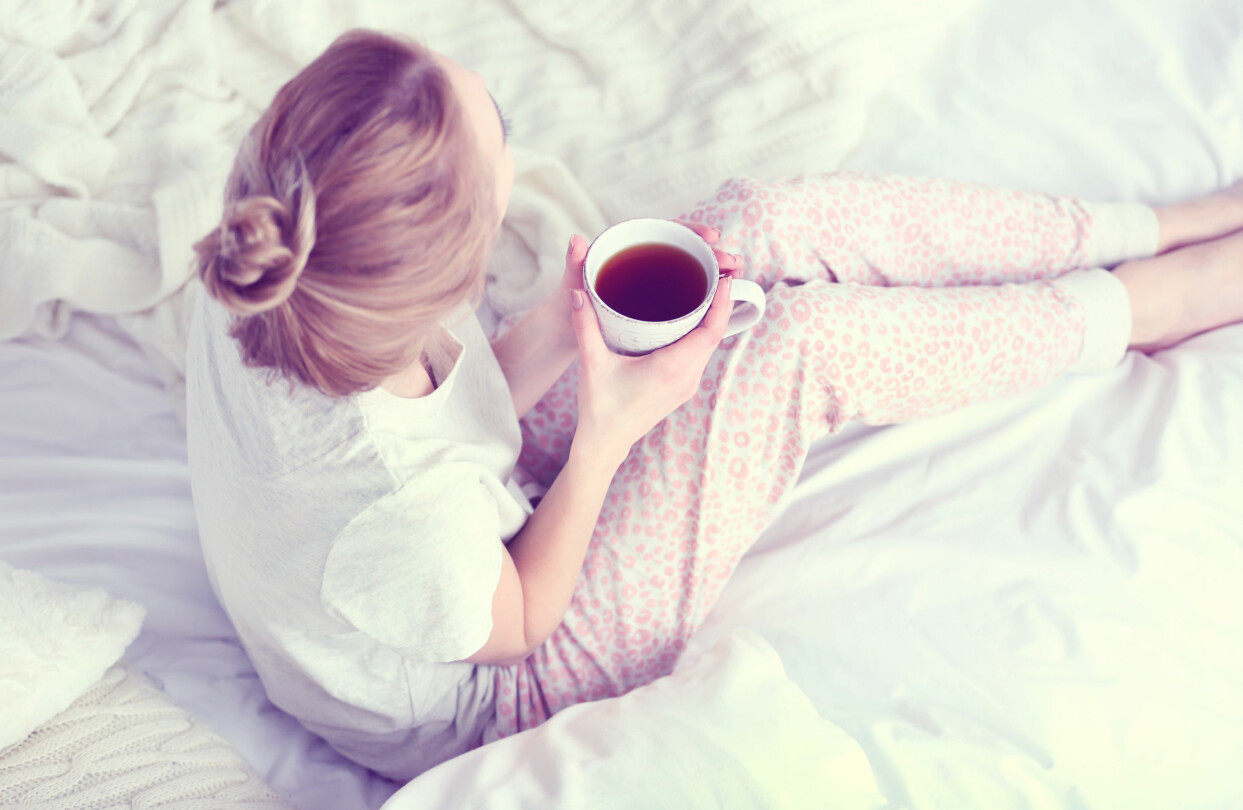 Kvinna sitter i en säng med en kopp te i handen.