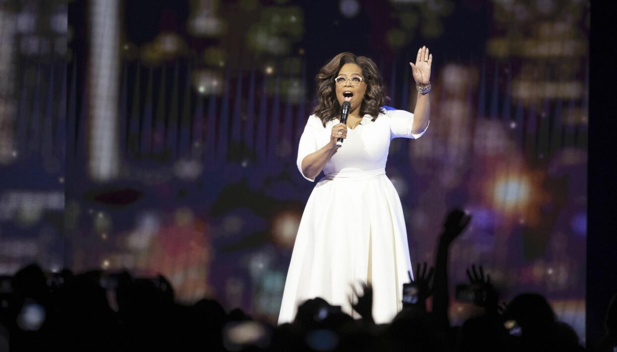 Programledaren Oprah Winfrey i vit klänning med en mikrofon i händerna.