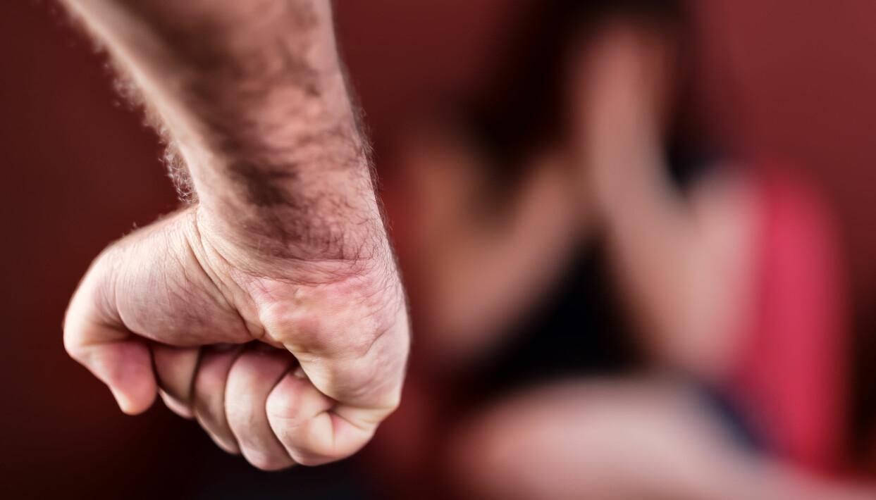 Hotfull man knyter näven framför rädd kvinna.