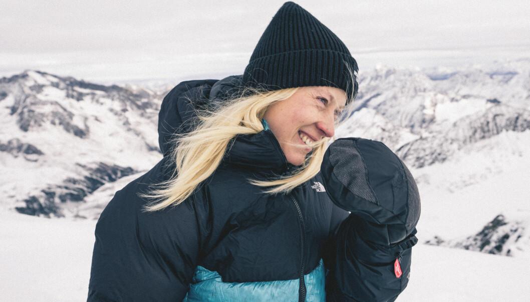 Emma ser lycklig ut på toppen av ett vintrigt berg.