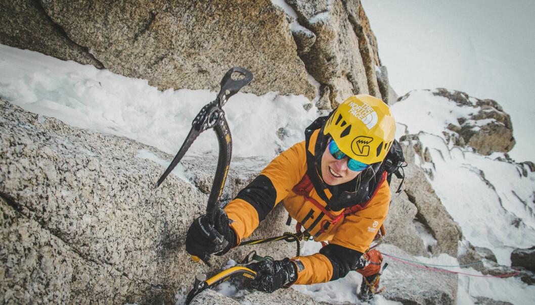 Emma i gul hjälm klättrat uppför ett snöigt berg.