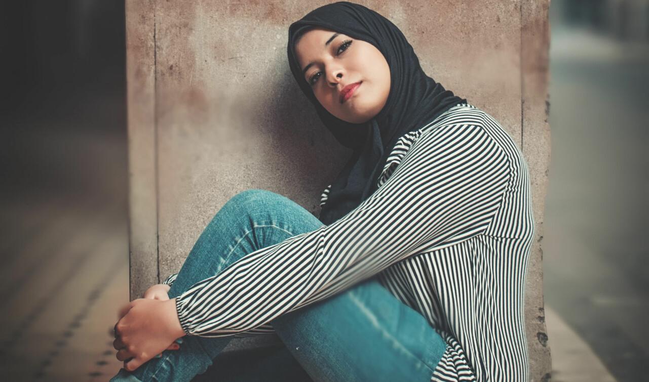 Porträtt av ung kvinna som sitter vid en betongpelare.