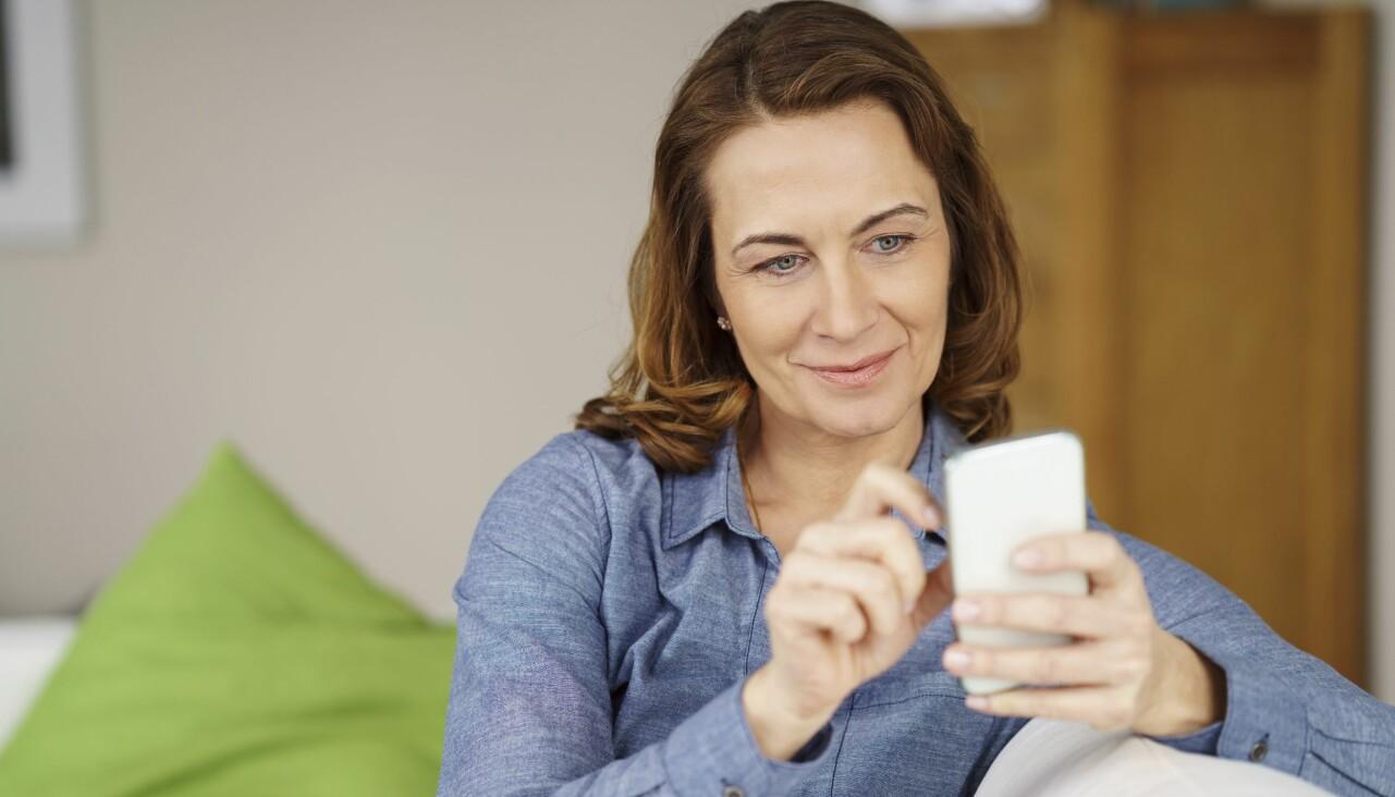Kvinna sitter med en mobiltelefon i handen.