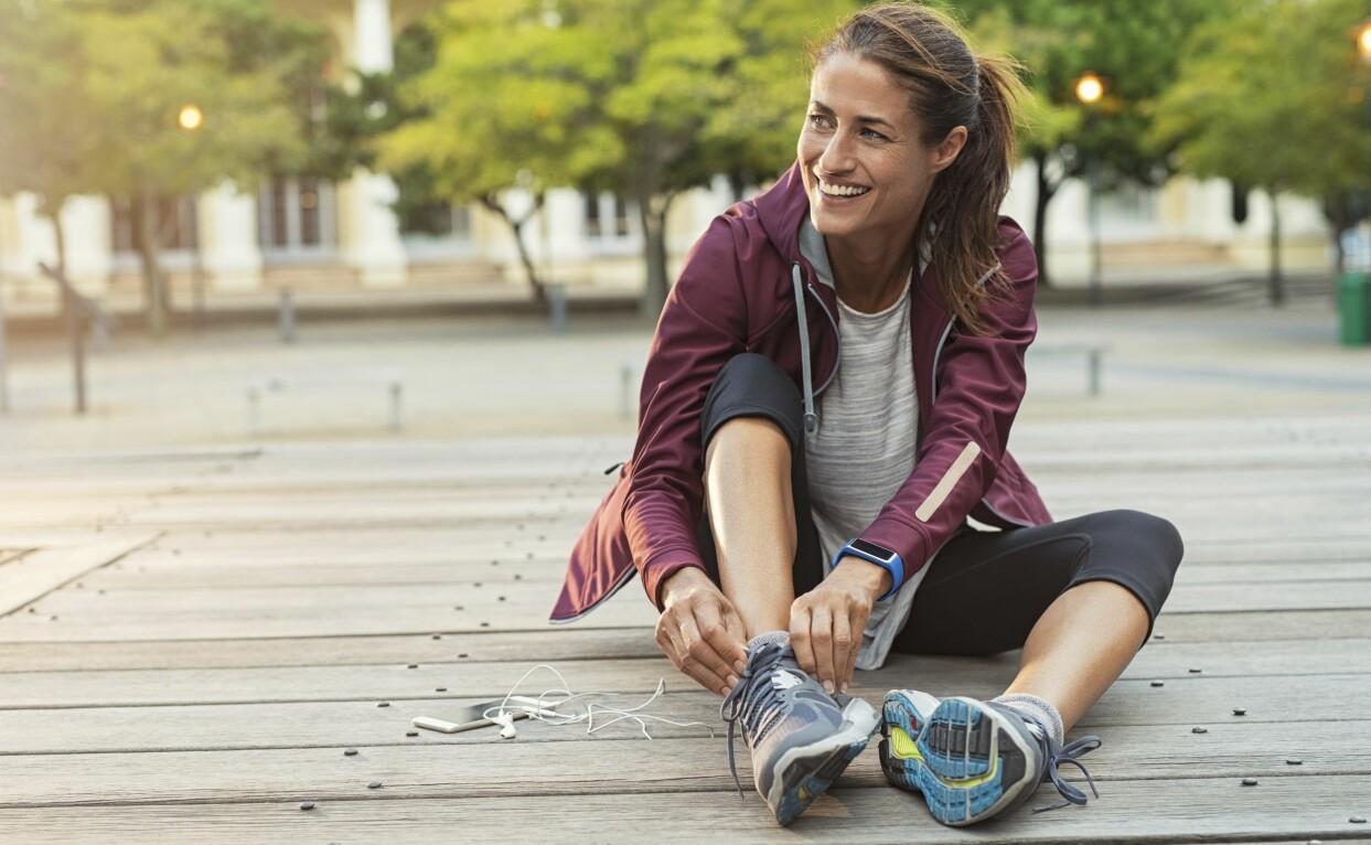 Kvinna snör på sig löparskorna inför ett pass.