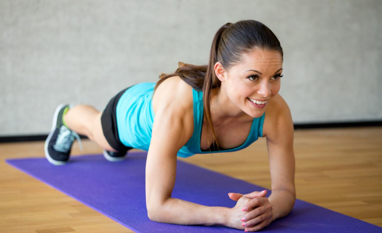 Kvinna tränar magen i plankövning.