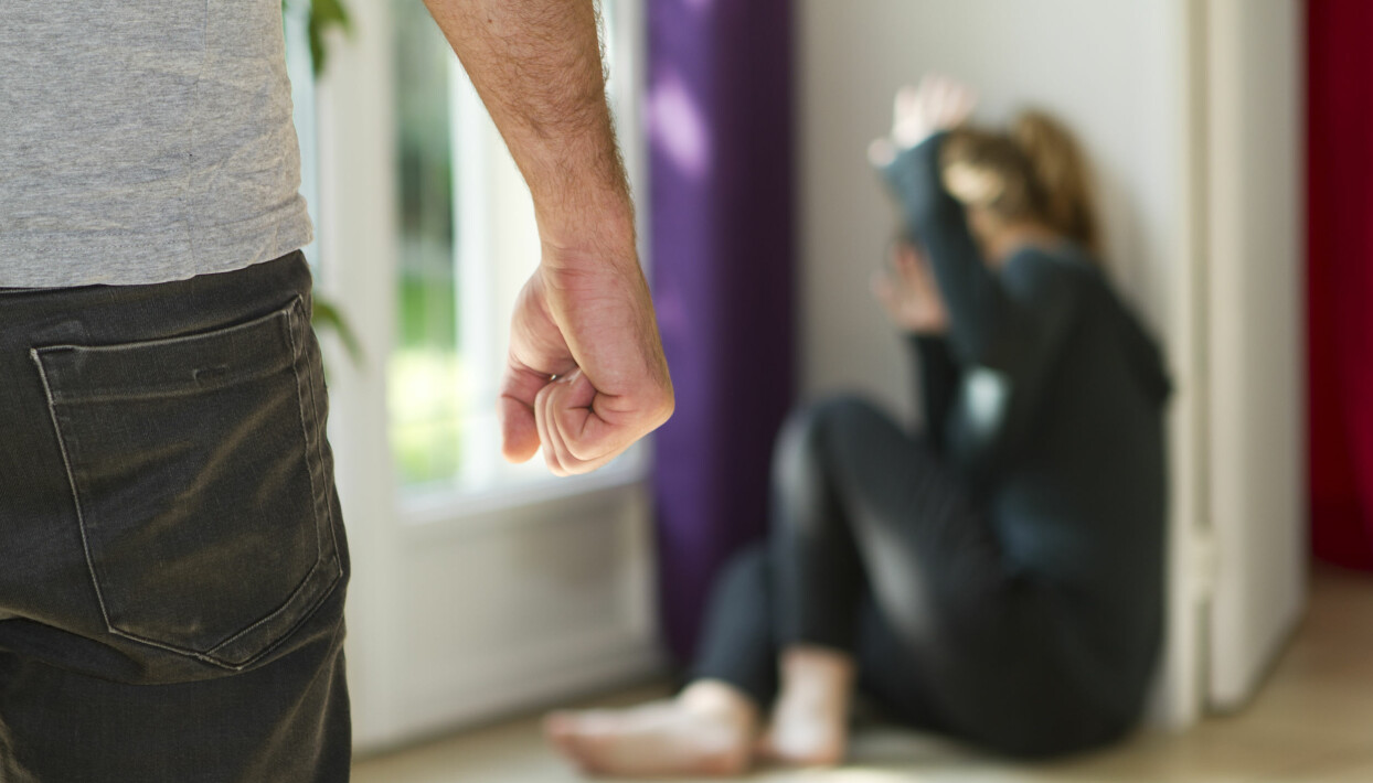 En man ar hotande med sin knytnave nar en kvinna sitter i ett horn i hemmet.