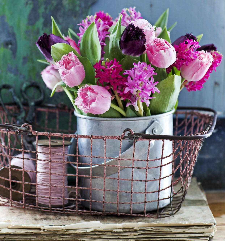 Bukett med franstulpaner och hyacinter i rostig korg.