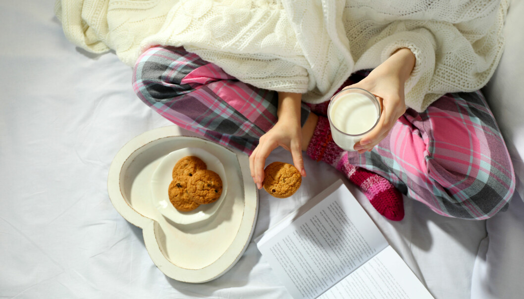 Kvinna i pyjamas tröstäter mat.