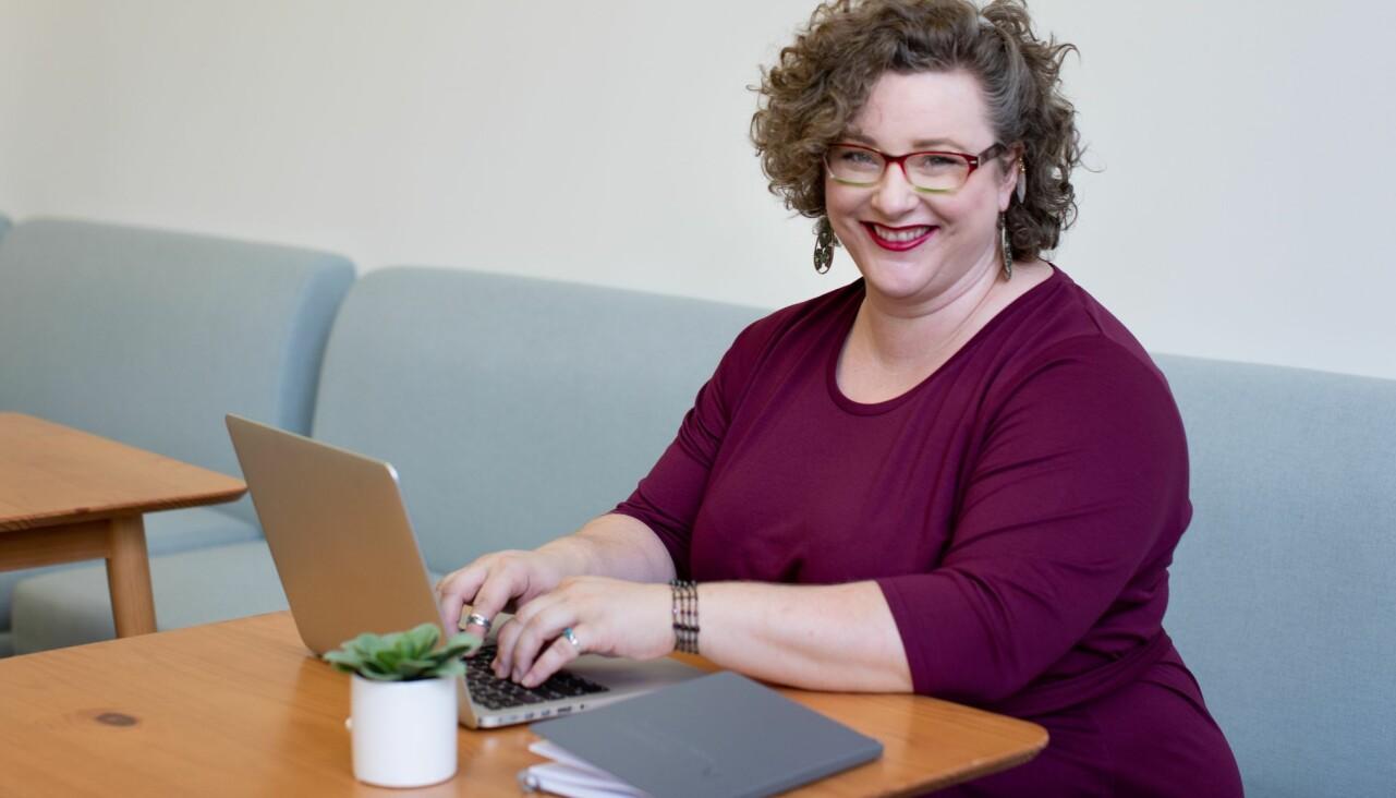 Kvinna sitter med sin dator och arbetar.