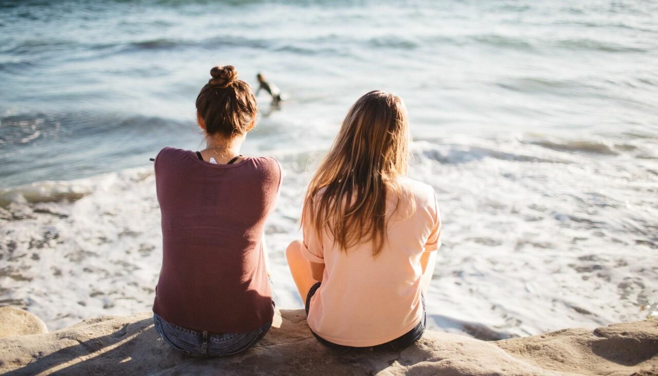 Två vänner sitter tillsammans på en strand.