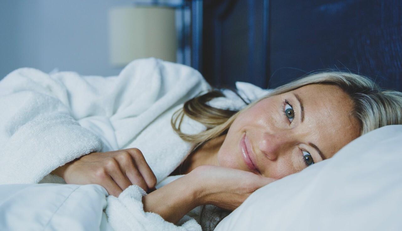 Kvinna ligger i en säng och ler mot kameran.