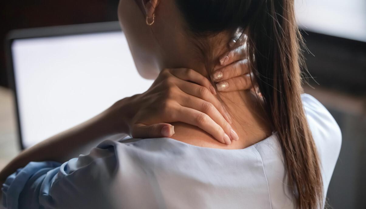 Kvinna håller sig för nacken.
