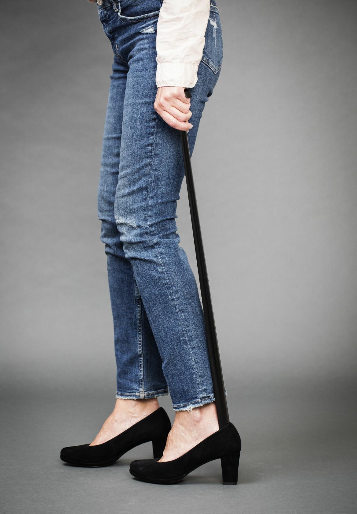 Kvinna använder långt skohorn när hon tar på sig skorna.