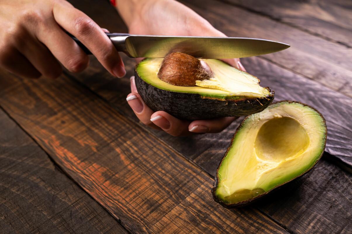 Kvinna skär loss en avokadokärna med en kniv.