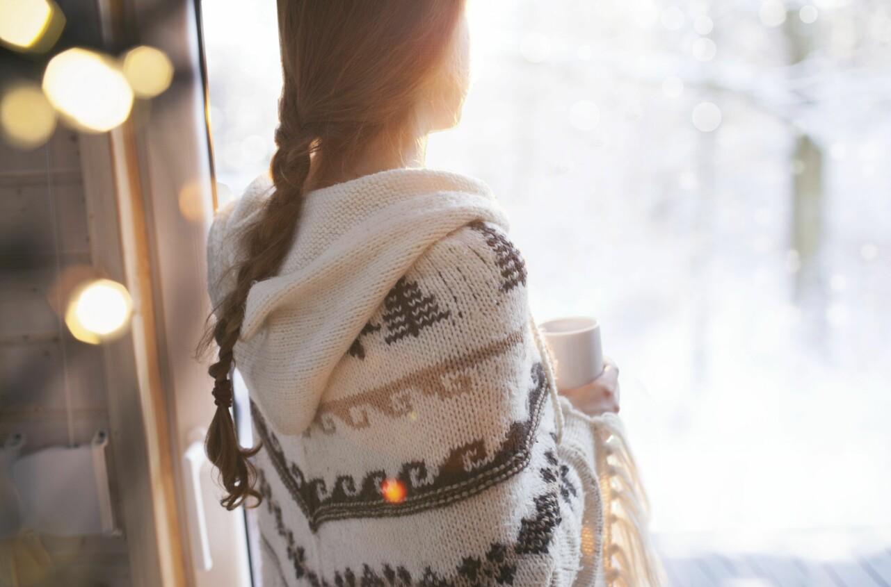 Kvinna som längtar efter barn står med ryggen mot kameran och tittar ut genom ett fönster.