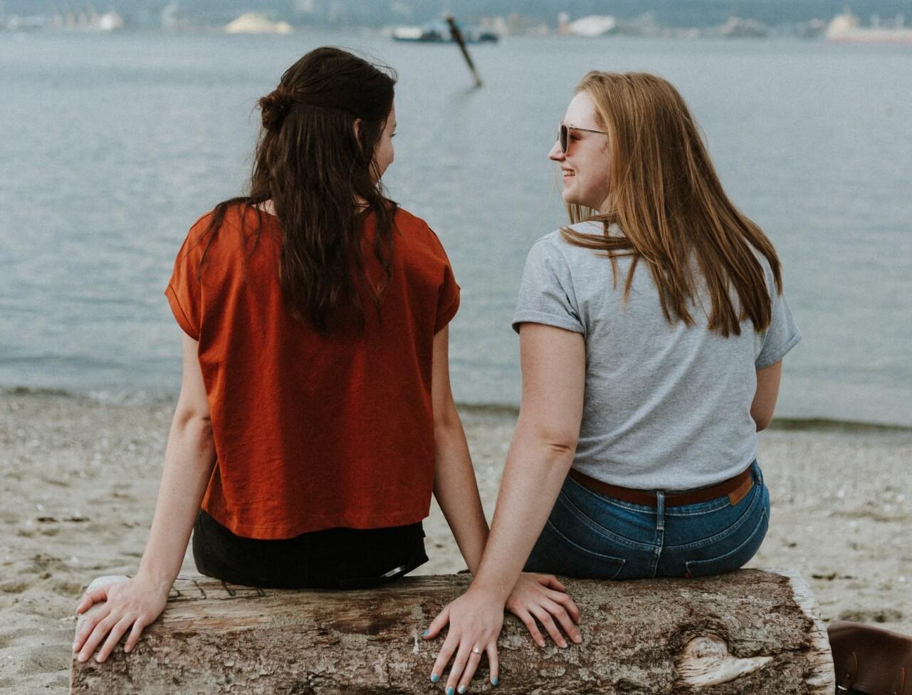 Två vänner sitter och pratar på en strand.