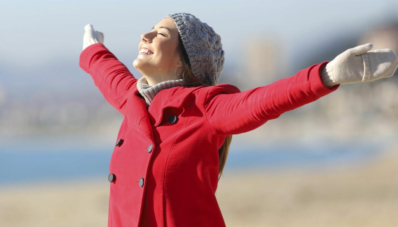 Kvinna sträcker ut armarna i luften och ser lycklig ut.