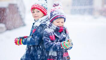 Två barn leker utomhus i snön.