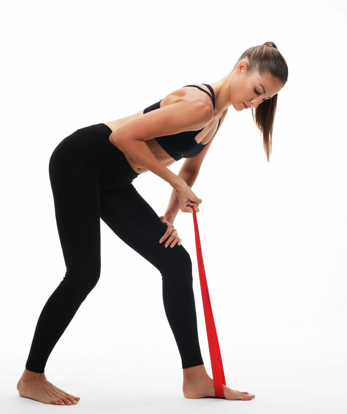 Kvinna tränar kroppen med gummiband.