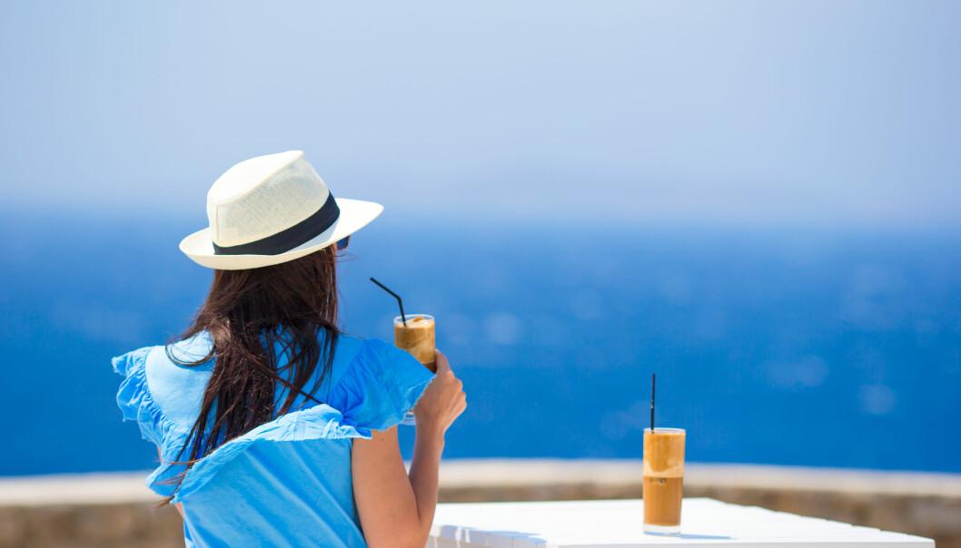 Kvinna dricker kaffe vid havet.