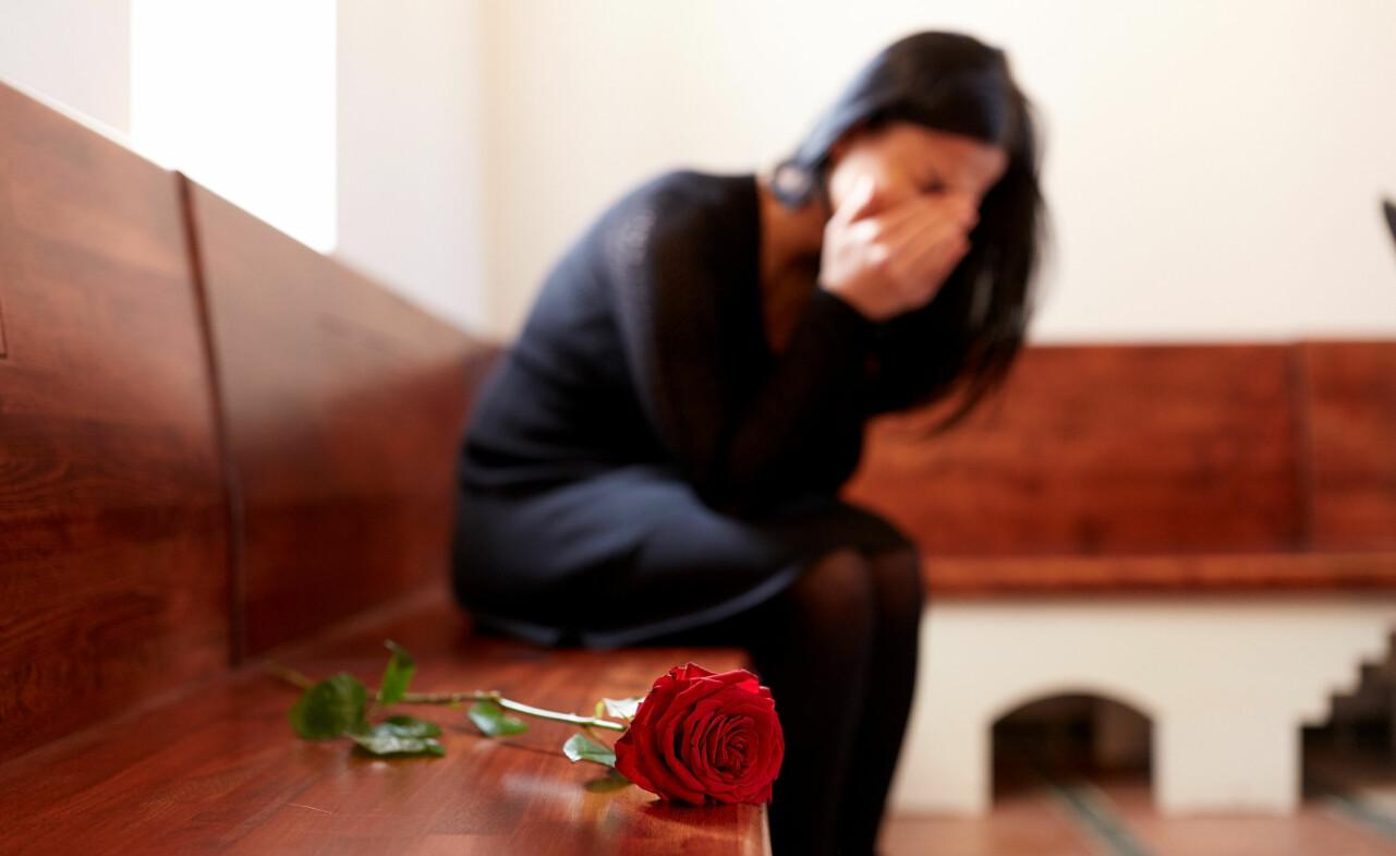 Kvinna gråter över sin mamma som precis dött.