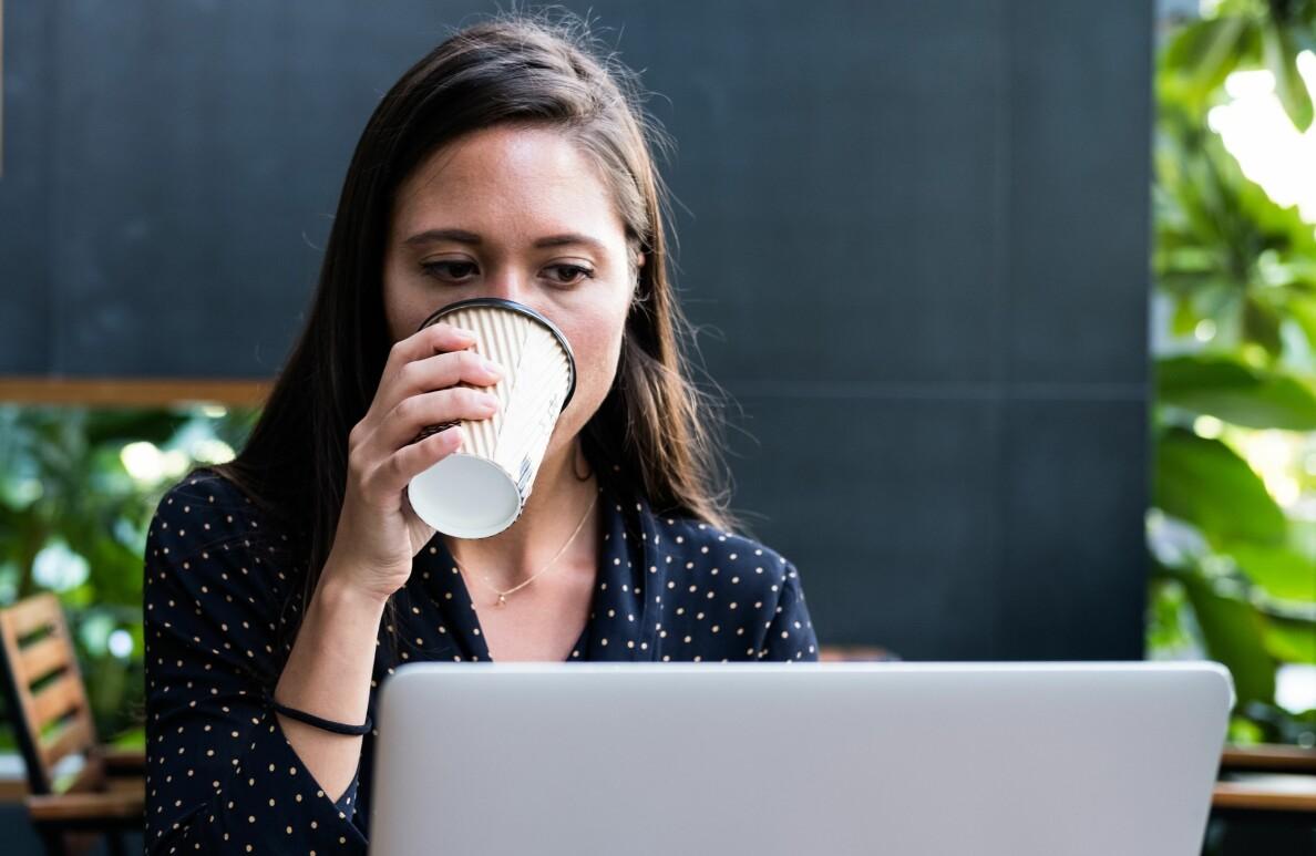Kvinna sitter vid sin dator och dricker kaffe.