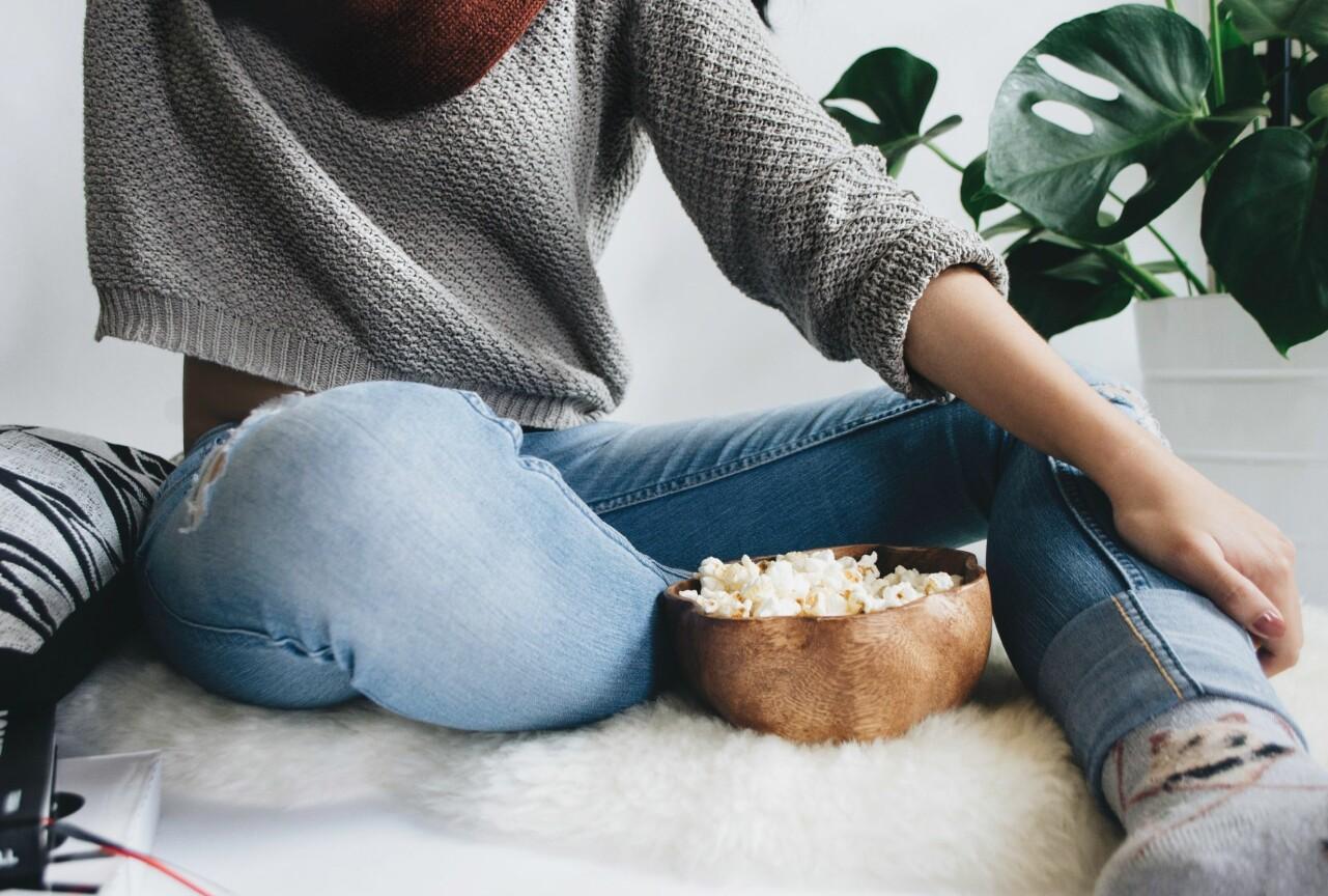 Kvinna äter popcorn.
