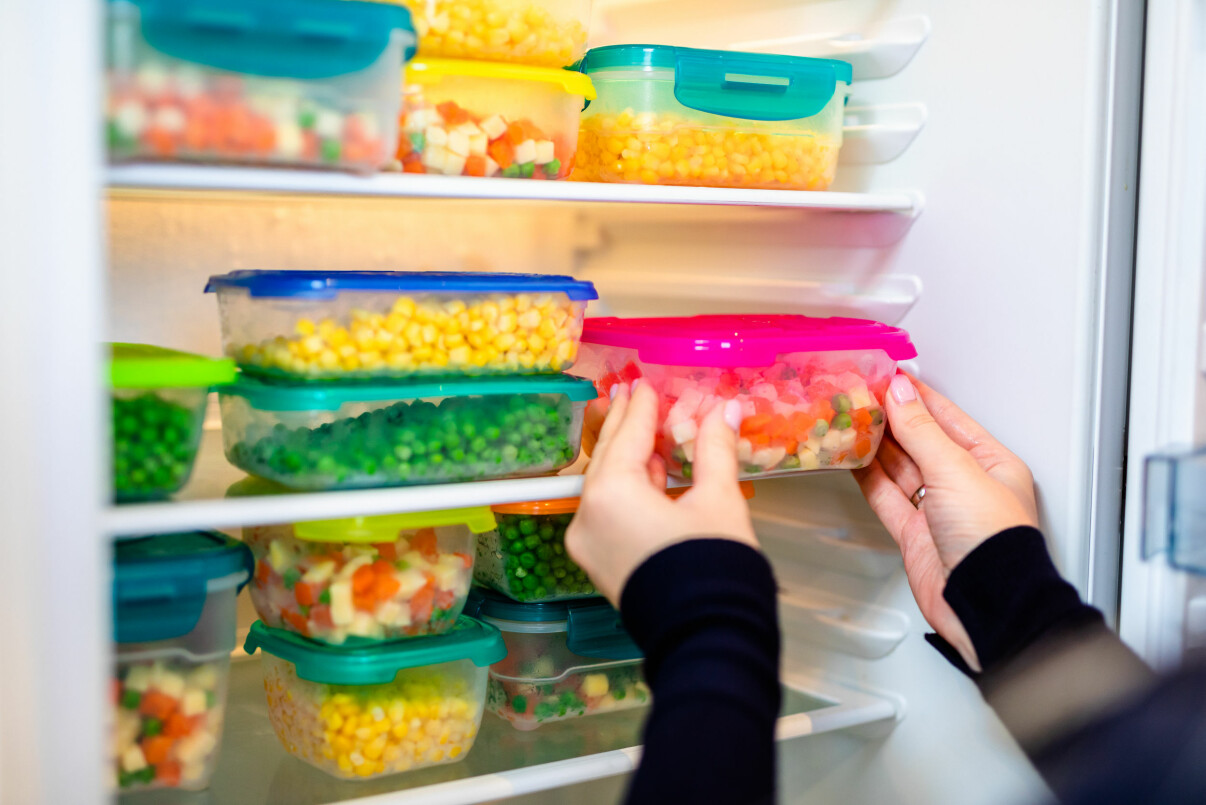 Kvinna lastar in matlådor i kylen.