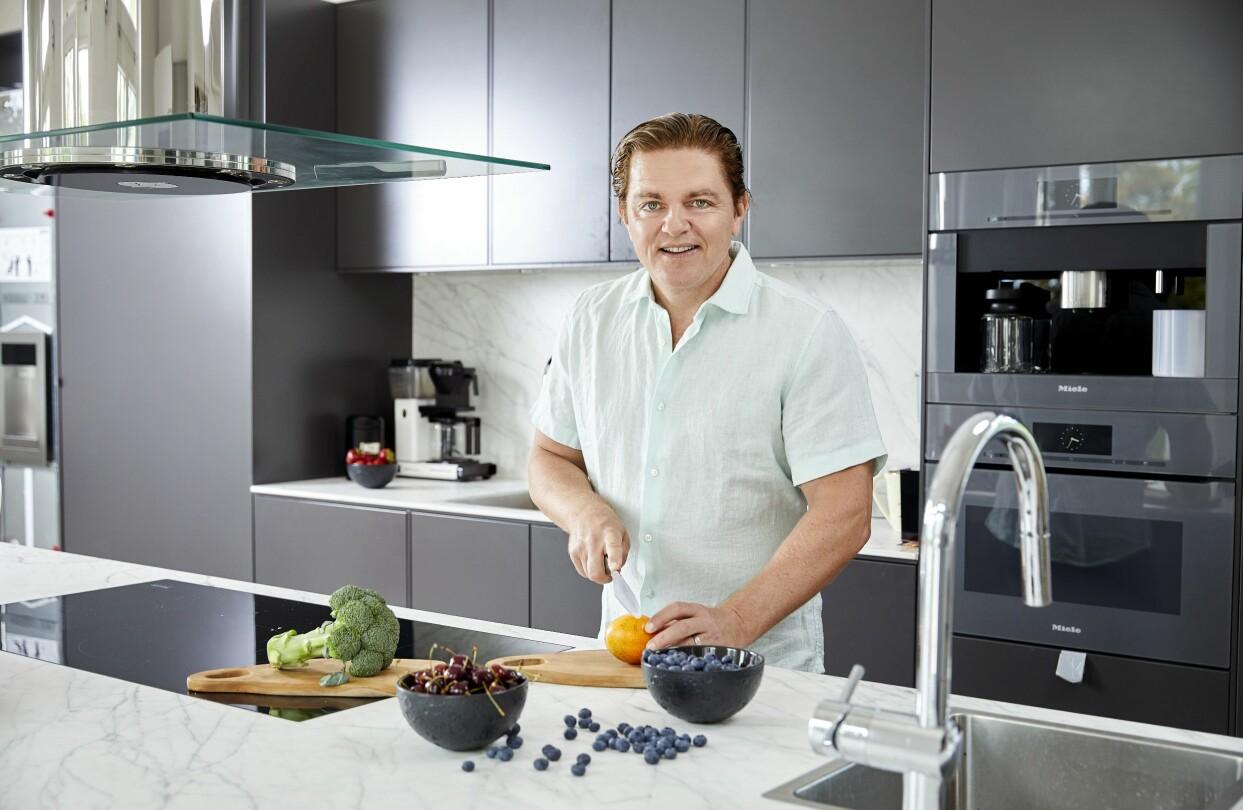 Fredrik Paulún är aktuell med en ny bok om biohack. Här står han i sitt kök och skär frukt och grönt.