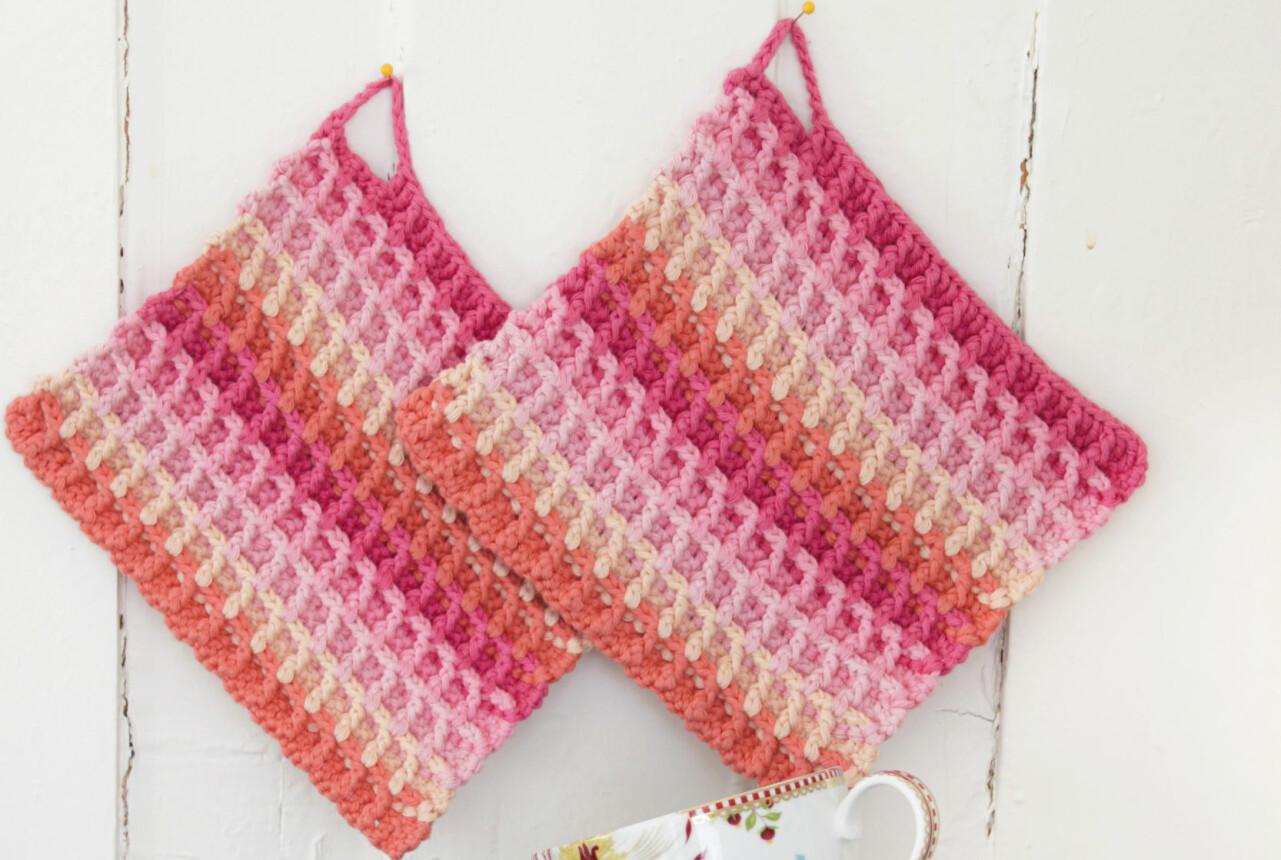 Virkade grytlappar med fint våffelmönster i rosa toner hänger på en vägg.