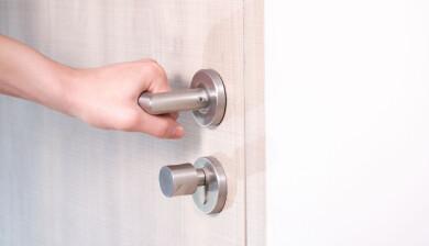Hand som tar i ett dörrhandtag för att se om dörren är låst.