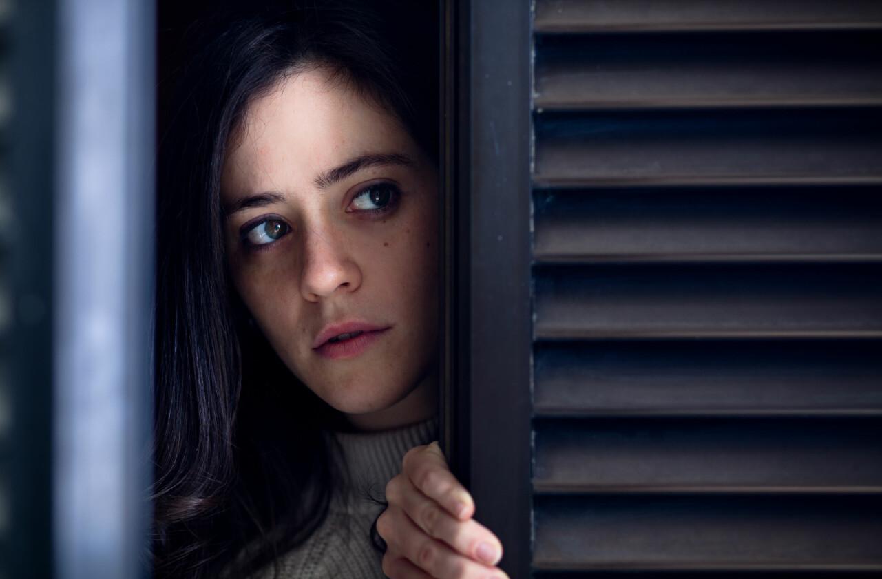 Kvinna i hemsökt hus tittar nervöst fram bakom ett fönster.